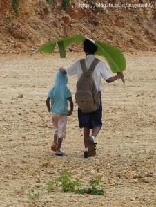 anak pulang sekolah kepanasan menggunakan daun pisang untuk penenduhnya